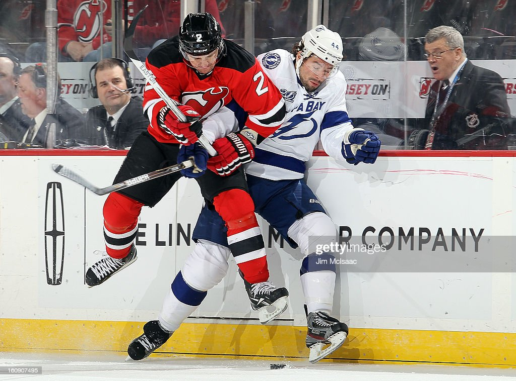 Marek Zidlicky #2 of the New Jersey Devils throws a first period check against Nate Thompson #44 of the Tampa Bay Lightning at the Prudential Center on February 7, 2013 in Newark, New Jersey.