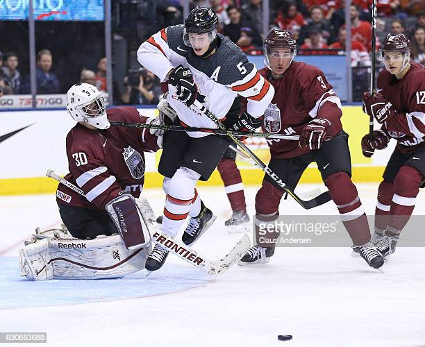 Mareks Mitens of Team Latvia takes a stick in the head from teammate Eduards Jansons while Thomas Chabot of Team Canada skates for the puck during a...