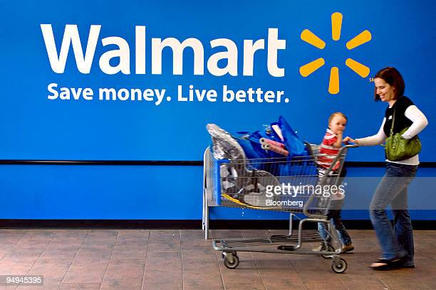 Maren Hufford right and her daughters Laney seated and Megan leave a WalMart Supercenter store in Rogers Arkansas US on Tuesday March 10 2009 WalMart...
