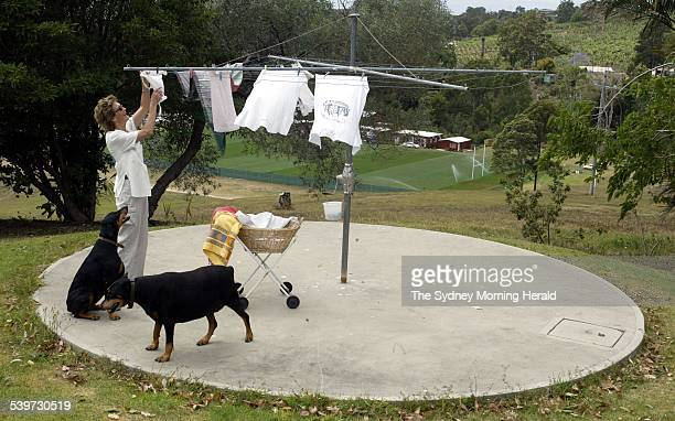 Margaret Beckett takes her clothes off the hills hoist while her dogs SERIOUS and YAHOO wait In the background is the Wallabies training oval at...