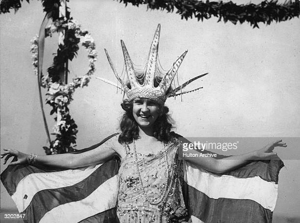 Margaret Gorman from Washington DC smiles wearing a large Statue of Liberty crown and a striped cape as the first Miss America Atlantic City New...