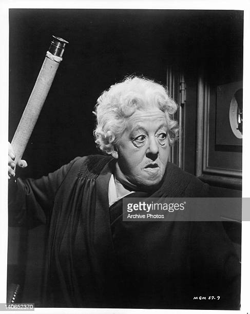Margaret Rutherford guards herself from prowlers with telescope in a scene from the film 'Murder Ahoy' 1964