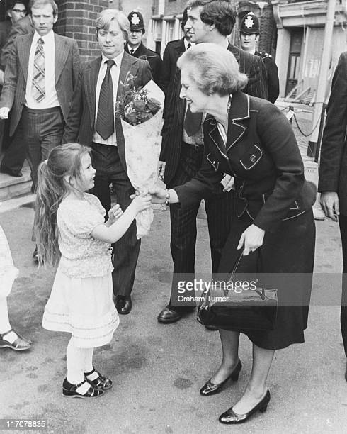 Margaret Thatcher Leader of the Conservative Party receives a bouquet of flowers from 4yearold Nancy Turner as she leaves the Greenwood Theatre on...