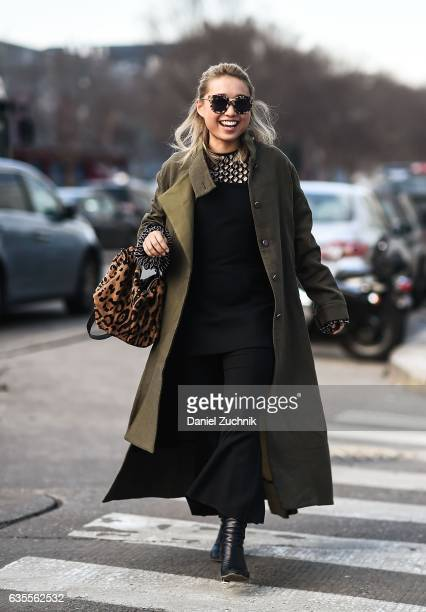 Margaret Zhang is seen wearing a green coat and black dress with animal print bag outside the Yeezy Kanye West show during New York Fashion Week on...
