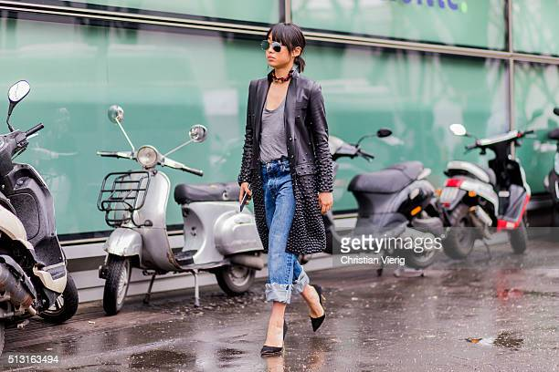 Margaret Zhang is wearing a black leather coat grey shirt blue denim jeans and black heels seen outside Giorgio Armani during Milan Fashion Week...