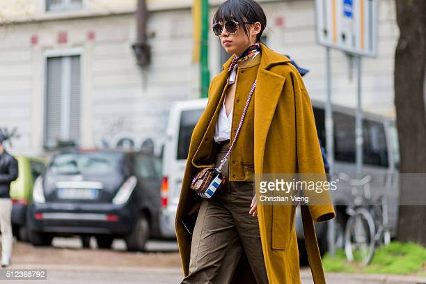 Margaret Zhang wearing a mustard coat and a Fendi bag seen outside Fendi during Milan Fashion Week Fall/Winter 2016/17 on February 25 in Milan Italy