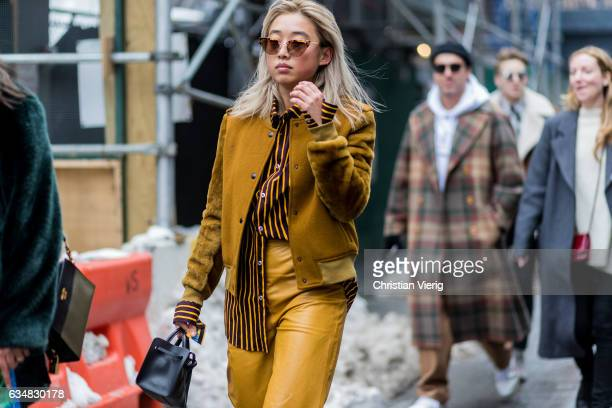 Margaret Zhang wearing a mustard jacket outside Tibi on February 11 2017 in New York City