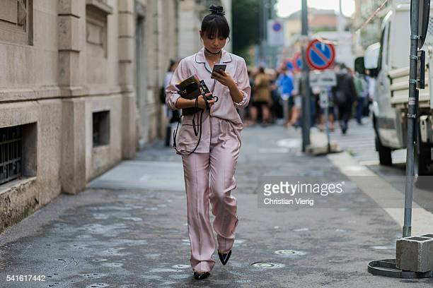 Margaret Zhang wearing a pink pyjama and Prada bag outside Prada during the Milan Men's Fashion Week Spring/Summer 2017 on June 19 2016 in Milan Italy