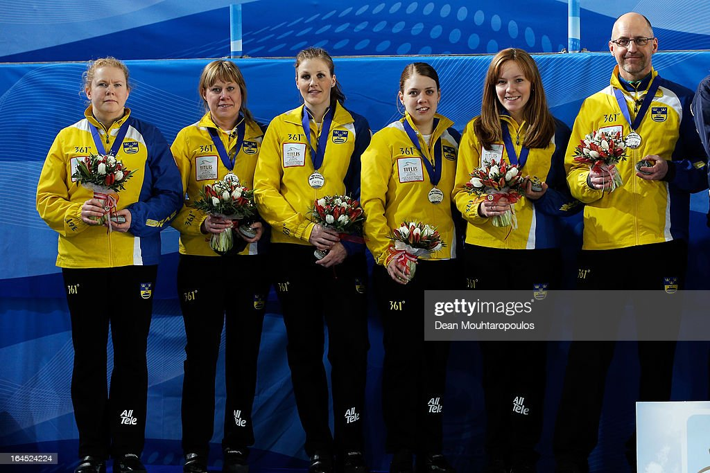 Margaretha Sigfridsson, Maria Prytz, Christina Bertrup, Maria Wennerstrom, Agnes Knochenhauer and coach, Fredrik Hallstrom of Sweden pose with the Silver medals after the Gold medal match between Sweden and Scotland on Day 9 of the Titlis Glacier Mountain World Women's Curling Championship at the Volvo Sports Centre on March 24, 2013 in Riga, Latvia.