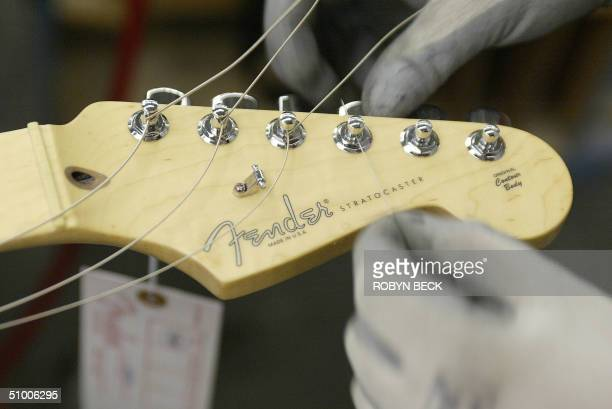 Margarita Fernandez strings a Fender Stratocaster guitar at the Fender manufacturing facility in Corona California 28 June 2004 The sainted...