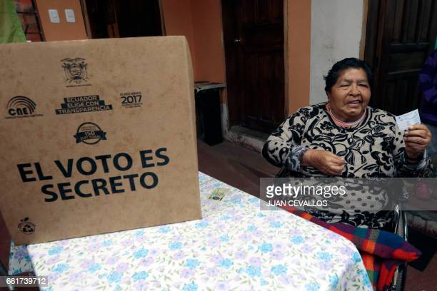 Margarita Guaman shows her voting certificate after casting his vote for Ecuador's presidential runoff at her house in the framework of the 'Vote at...
