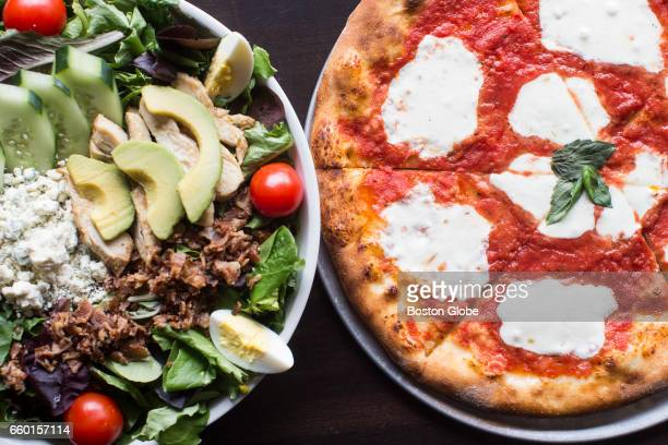Margherita pizza and a cob salad sit on a table at Stone L'Oven in Newton MA on Mar 21 2017