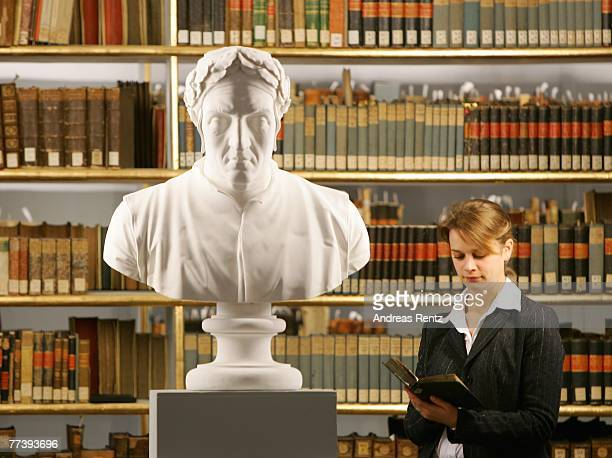 Margit Adler reads a book near the sculpture of Italian poet Dante at the historic Rococo room of the Duchess Anna Amalia Library on October 18 2007...