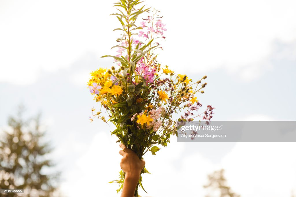 Mari boy holding up bouquet of flowers outdoors