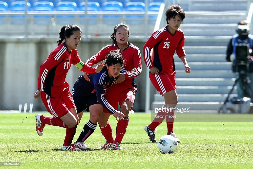 Mari Kawamura of Japan challenges Pu Wei and Wang Lisi of China during the Algarve Cup 2013 fifth place match at the Estadio Algarve on March 13, 2013 in Faro, Portugal.