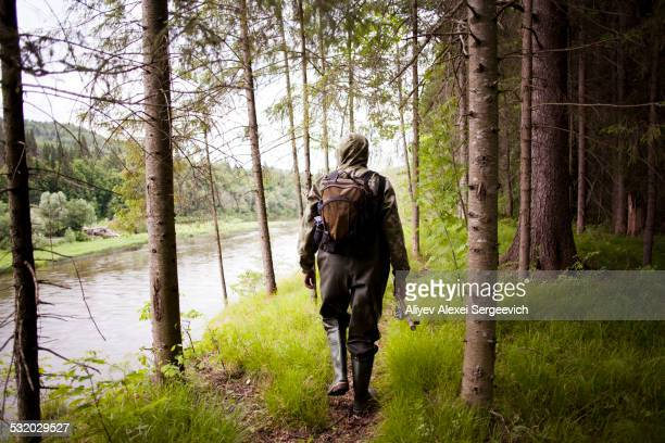 Mari man in wading boots walking near river in forest