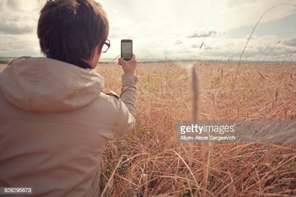 Mari man photographing rural field with cell phone