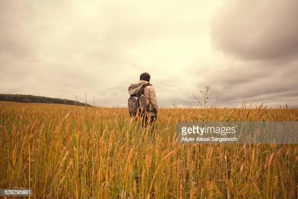 Mari man standing in tall grass in rural field