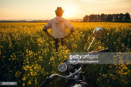 Mari man standing near motorcycle in field of flowers