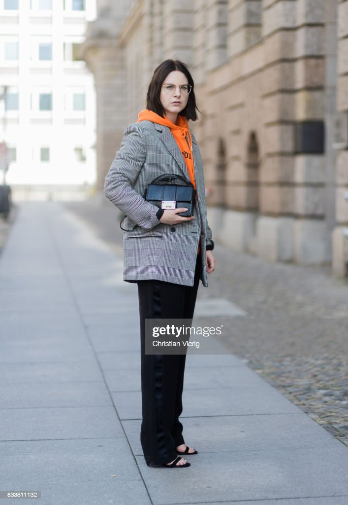 Maria Barteczko wearing orange hoodie Wasted Paris, oversized checked blazer in grey Stella McCartney, wide leg black trousers H&M, black heels Gianvito Rossi, black python printed bag Jimmy Choo, round glasses Ray Ban on August 17, 2017 in Berlin, Germany.