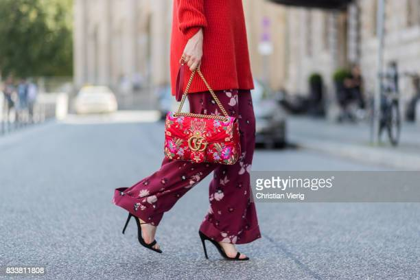 Maria Barteczko wearing red oversized wool sweater The Row flared floral trousers Valentino black heels Gianvito Rossi red GG Marmont flower printed...