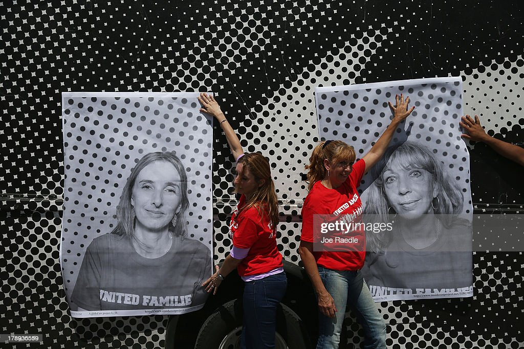 Maria Bilboa (L) and Sandra Bisso hold up photographs of themselves as they participate in the 'Inside Out 11M' project on August 31, 2013 in Miami, Florida. The public art project puts a face on immigration reform by creating a massive mosaic of portraits taken on site, printed immediately and pasted on the Freedom Tower at Miami-Dade College.
