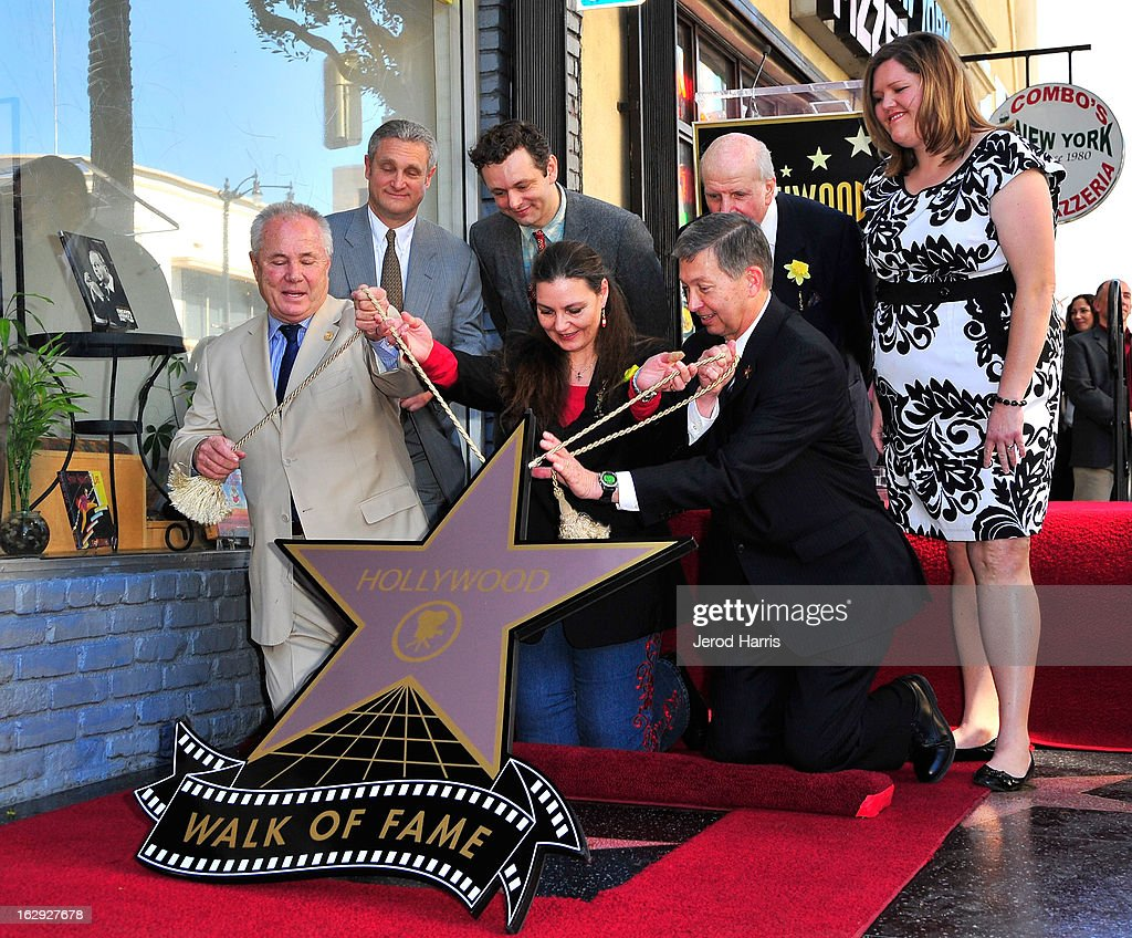Maria Burton (C) lifts the plaque covering her father Richard Burton's Star on the Hollywood Walk of Fame on March 1, 2013 in Hollywood, California.