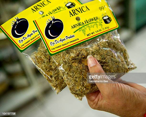 Maria Dorais of Sacramento holds bags of Arnica flower August 26 which she said she will use as a rub on sore muscles after letting it sit for a...