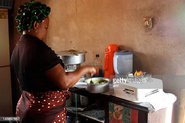 Maria Doua of Mozambique cooks indoors with an ethanolfueled cooking stove in the Mozambican capital Maputo on May 19 2012 Until now charcoalfueled...