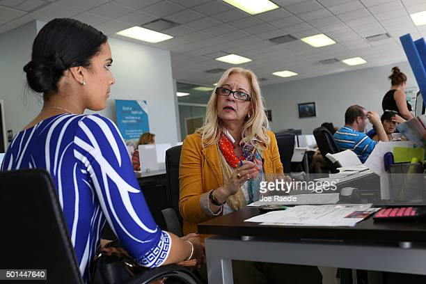 Maria Elena Santa Coloma an insurance advisor with UniVista Insurance company helps Shessy Gonzalez sign up for a health plan under the Affordable...