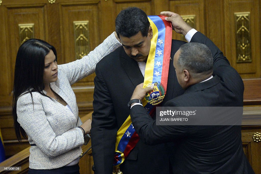 Maria Gabriel Chavez(L) daughter of late Venezuelan president Hugo Chavez and the President of the National Assembly Diosdado Cabello(R) put the ceremonial sash to the President Nicolas Maduro during the Presidential inaguration ceremony in Caracas on April 19, 2013.