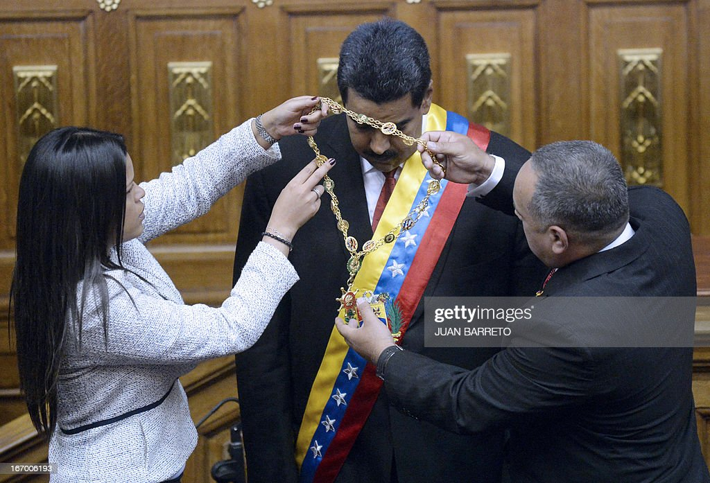 Maria Gabriela Chavez (L) daughter of late Venezuelan president Hugo Chavez and the President of the National Assembly Diosdado Cabello (R) decorate President Nicolas Maduro during the Presidential inaguration ceremony in Caracas on April 19, 2013.