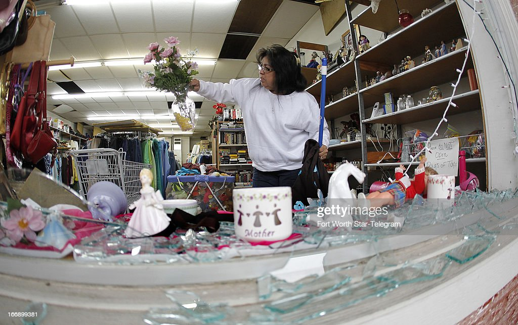 Maria Galvan looks at damaged merchandise as she cleans up at a store in West, Texas, on Thursday, April 18, 2013. Much of the small town suffered damage when a fertilizer plant caught fire causing a massive explosion Wednesday night. Authorities are still trying to determine the death and injury toll.