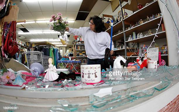 Maria Galvan looks at damaged merchandise as she cleans up at a store in West Texas on Thursday April 18 2013 Much of the small town suffered damage...