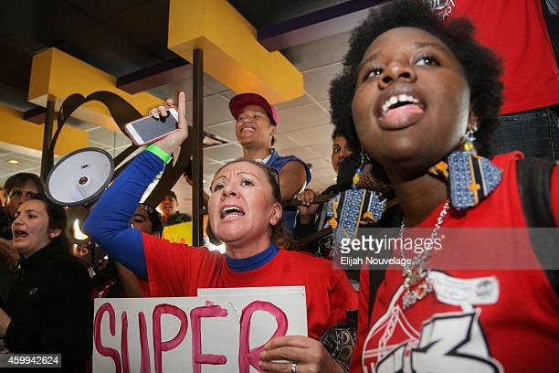 Maria Garcia center and Rhonesha Victor right take part in a demonstration for higher wages and better security for fast food workers inside a Taco...