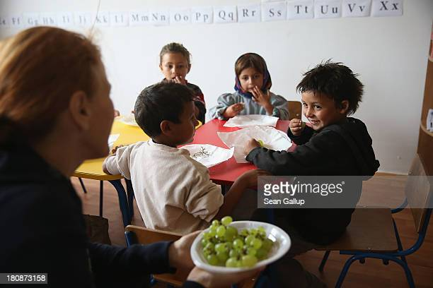 Maria Gheorghiu cofounder of the Romanian NGO OvidiuRo offers Roma children grapes during snacktime in the preschool class in the abjectly poor Roma...
