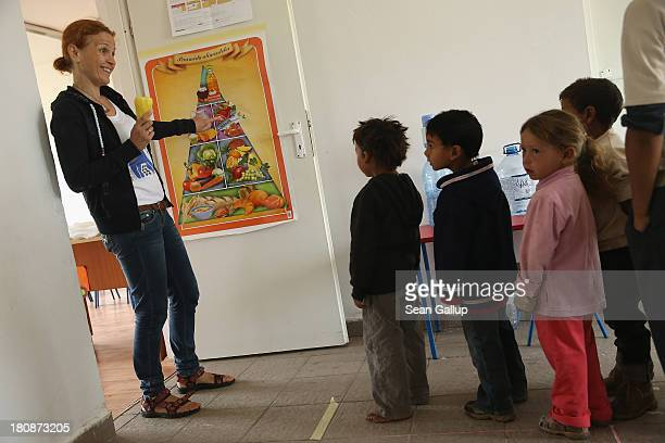 Maria Gheorghiu cofounder of the Romanian NGO OvidiuRo prepares young Roma children for snacktime in the preschool class in the abjectly poor Roma...