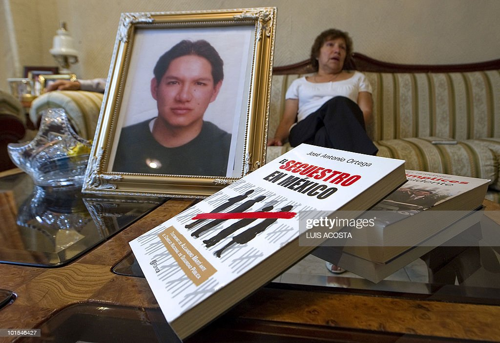 BARROS - Maria Guadalpe Fernandez speaks with AFP behind the portrait of her kidnapped son Jose Antonio Robledo, during an interview in Mexico City on, May 20, 2010. Mexican engineer Jose Antonio Robledo was kidnapped 16 months ago and his parents regret having entrusted the case to the police. Like other family members of kidnapped Mexicans, they question the effectiveness of authorities. AFP PHOTO/Luis Acosta