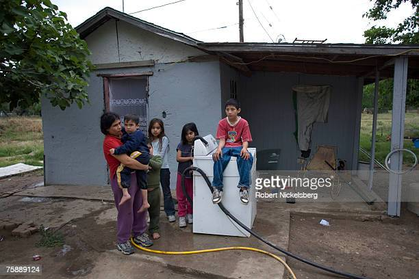 Maria Guadelupe Pena left a Hispanic mother of five children stands with her family outside of her two room house in a lower income neighborhood on...