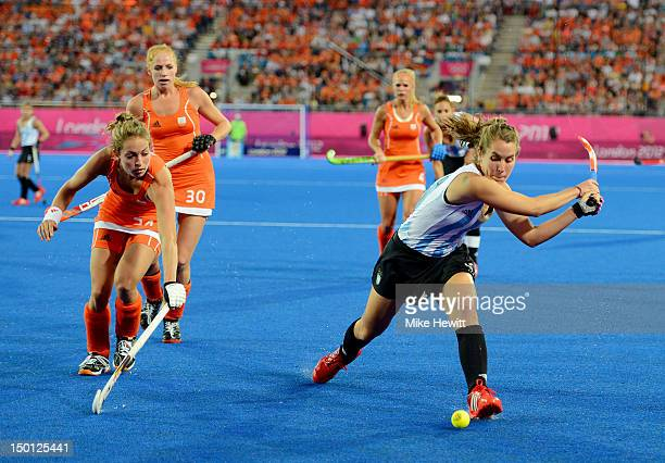 Maria Josefina Sruoga of Argentina moves the ball against Eva De Goede of Netherlands during the Women's Hockey gold medal match on Day 14 of the...