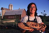 Maria Lammers holding freshly baked cherry pies at her Gallagher's farm market bakery gearing up for Natl Cherry Festival at which local bakers can...