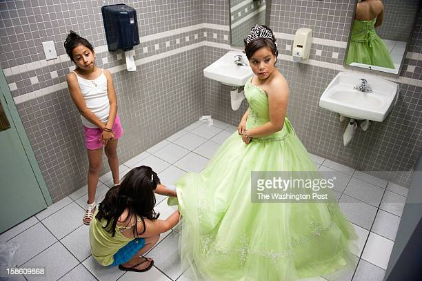 Maria LopezGarcia right of Lanham gets dressed in the bathroom of the Langley Park Community Center with her sister Yesenia Lopez and mother Leticia...