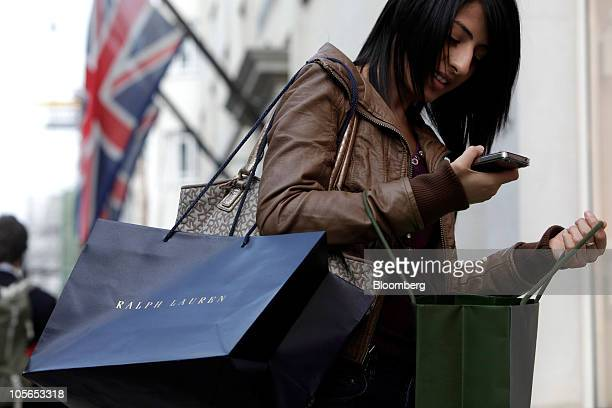 Maria Patel poses for a photograph holding an Apple Inc iPhone 4 and Ralph Lauren shopping bag in New Bond Street in London UK on Monday Oct 18 2010...