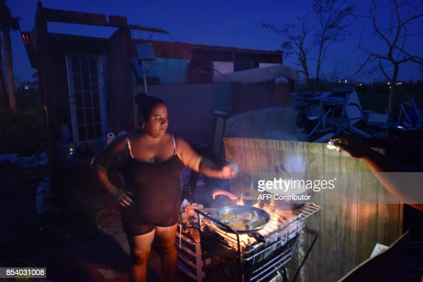 Maria prepares food during nightfall next to her home destroyed by Hurricane Maria in Toa Alta Puerto Rico on September 25 2017 The US island...