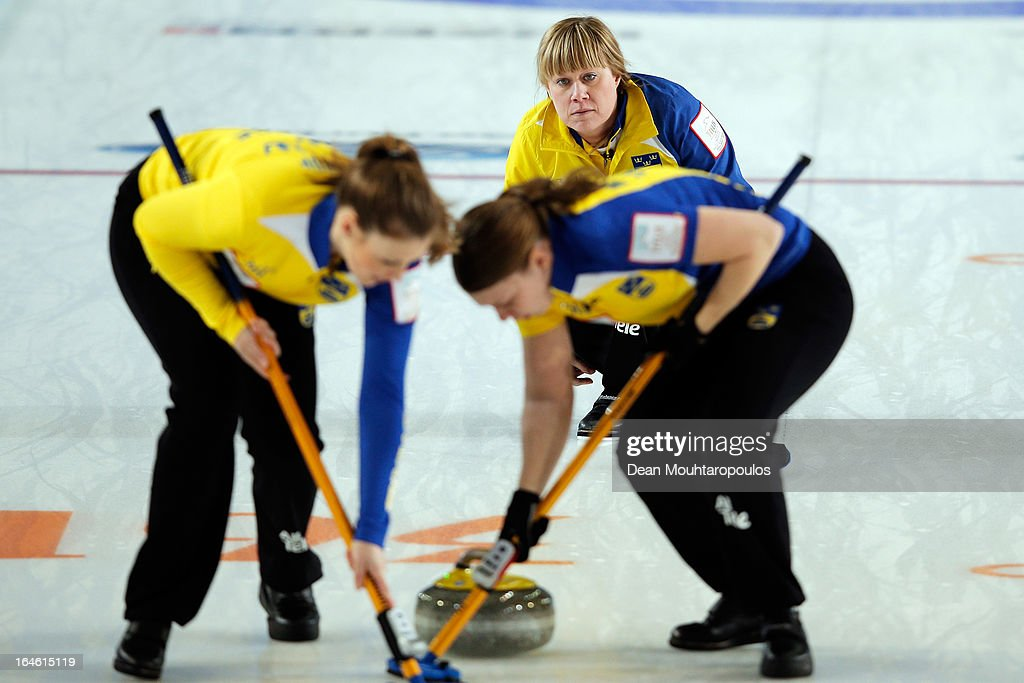 Maria Prytz (C) of Sweden looks on after she throws a stone as Christina Bertrup (L) and Maria Wennerstrom (R) sweep during the Gold Medal match between Scotland and Sweden on Day 9 of the Titlis Glacier Mountain World Women's Curling Championship at the Volvo Sports Centre on March 24, 2013 in Riga, Latvia.