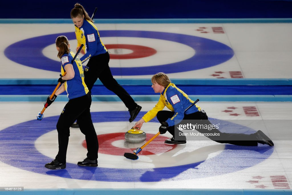 Maria Prytz (R) of Sweden throws a stone as Maria Wennerstrom (L) and Christina Bertrup (C) get ready to sweep during the Gold Medal match between Scotland and Sweden on Day 9 of the Titlis Glacier Mountain World Women's Curling Championship at the Volvo Sports Centre on March 24, 2013 in Riga, Latvia.