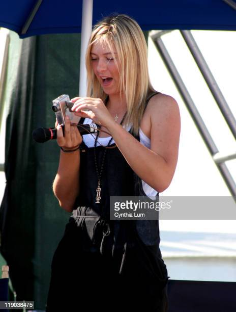 Maria Sharapova checks out a camera during a personal appearance endorsing Cannon Cameras at the Pacific Life Open Indian Wells California March 10...