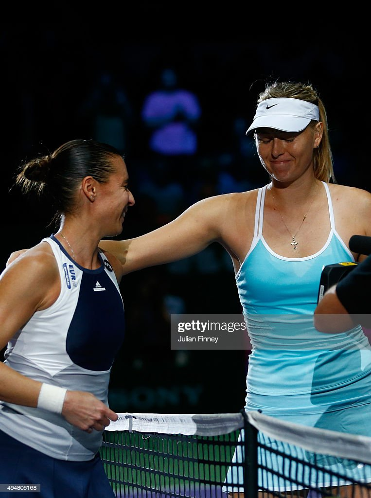 Maria Sharapova of Russia consoles Flavia Pennetta of Italy at the net after a straight set victory in a round robin match during the BNP Paribas WTA Finals at Singapore Sports Hub on October 29, 2015 in Singapore.
