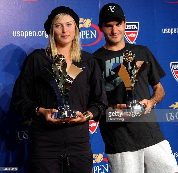 Maria Sharapova of Russia left and Roger Federer of Switzerland pose with their 2006 US Open championship trophies during a news conference at the...