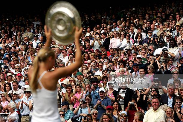 Maria Sharapova of Russia lifts her trophy as the crowd applauds her after her victory against Serena Williams of USA in the ladies final match at...
